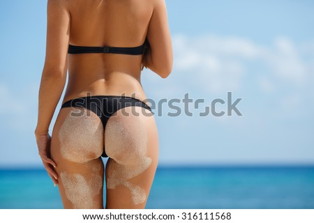 Sexy sandy woman buttocks on tropical beach background near ocean. close up outdoor shot of young woman in white bikini, sunbathing at sea shore. Black bikini on ocean background - stock photo