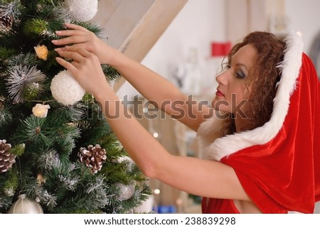 Sexy Santa Claus girl putting Christmas ornaments on the tree - stock photo