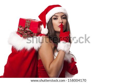 Sexy santa claus woman with christmas sack saying shh - stock photo
