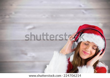 Sexy santa girl listening to music against blurred wooden planks - stock photo