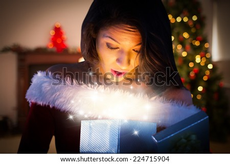 Sexy santa girl opening gift against christmas at home