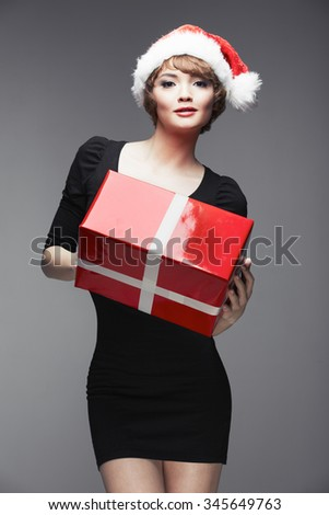 Sexy Santa girl posing with red gift box. Black dress. Beautiful female model.