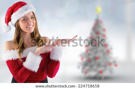 Sexy santa girl presenting with hands against blurry christmas tree in room - stock photo