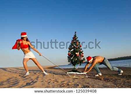 Sexy Santa helper  pulling Santa on a sled with Christmas tree at the beach.  (concept: Tropical winter fun) - stock photo