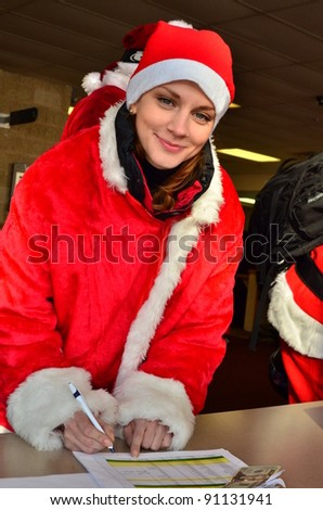 Sexy santa helper signing release form - stock photo