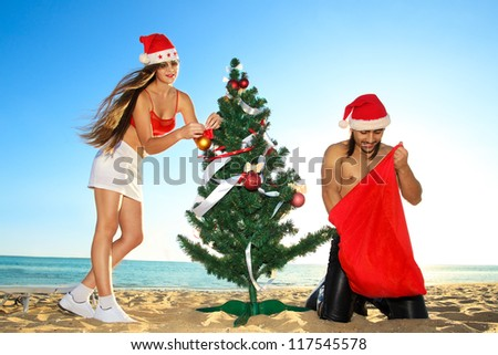 Sexy Santa's helper decking the Christmas tree and Santa looking into the sack at the tropical beach - stock photo