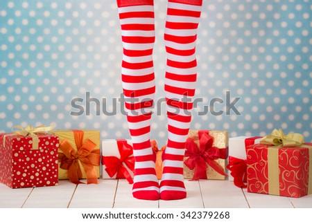 Sexy Santa woman legs. Christmas shopping concept. Xmas gift box - stock photo