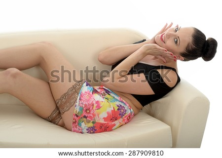 Sexy Sensual Pin Up Image of a Beautiful Attractive Young Caucasian Woman Wearing A Short Mini Skirt Pulled Up Revealing Here Stocking Tops and Thighs Shot Against White - stock photo