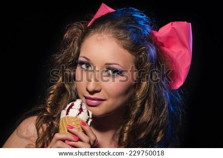 Sexy sensual woman in a pink bikini with ice-cream on black background - stock photo