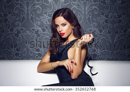 Sexy sensual woman with red lips holding handcuffs, sit on sofa at vintage wall at night, red lips and nails, bdsm - stock photo