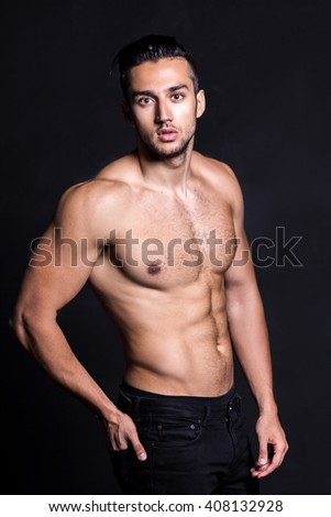 Sexy shirtless male model flirting against black background - stock photo