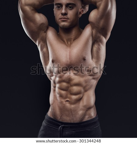 Sexy shirtless male model young bodybuilder posing over black background. Studio shot on black background. - stock photo