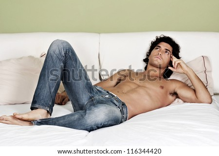 Sexy shirtless young man lying on bed in thinking pose