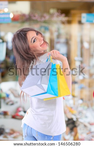 Sexy shopping girl holding bags  at the shoe shop - stock photo