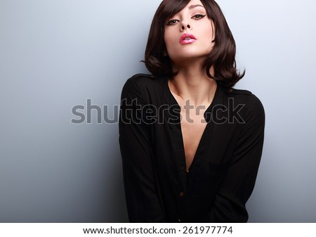 Sexy short hair female model posing in black shirt on blue background