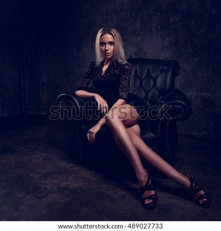 Sexy slim blond model sitting in fashion armchair in black dress and posing on dark shadow background. Drama light portrait. Toned