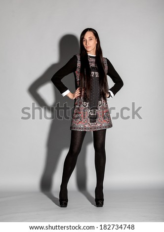 Sexy slim brunette woman with long hair standing at studio against grey background