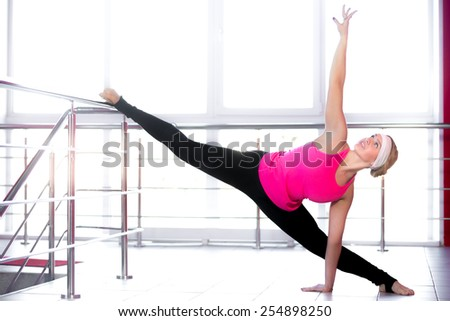 Sexy smiling dancer girl wearing pink gym t-shirt working out on dance technique, standing in choreography posture, doing splits - stock photo