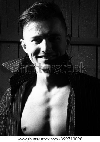 Sexy smiling sensual muscular young macho man with bare torso and wet hair in shirt standing indoor on wooden background, vertical picture - stock photo