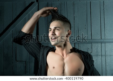 Sexy smiling sensual muscular young macho man with bare torso and wet hair in shirt standing with raised hands indoor on wooden background, horizontal picture - stock photo