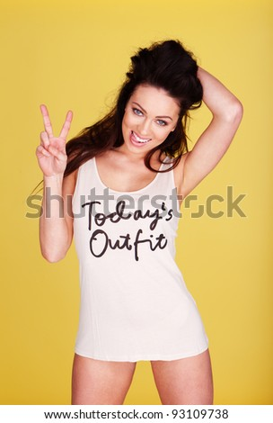 Sexy smiling woman giving the V sign with her fingers dressed in skimpy outfit isolated on yellow. - stock photo