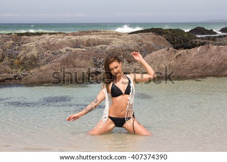 Sexy,smiling woman in bikini sitting in the sea posing for the camera with copyspace - stock photo