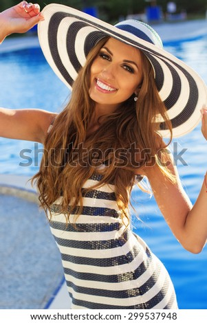 Sexy smiling woman is wearing stripped fashion dress and hat with tanned skin and perfect figure is standing near pool