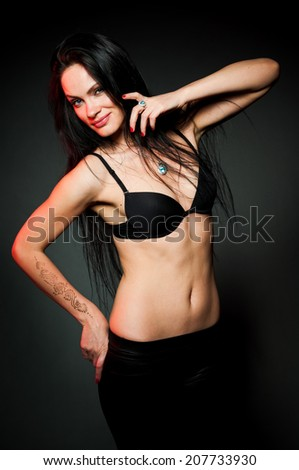 Sexy sport woman on gray background with red backlight