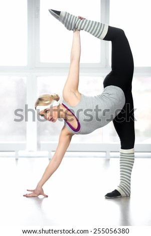 Sexy sporty female doing stretching exercises standing in splits during fitness or dance lesson in class in sport club - stock photo