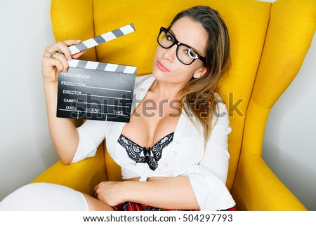 sexy student with plaid skirt and white shirt holding a clapperboard
