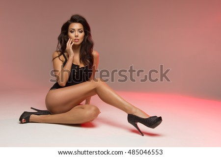 Sexy stylish brunette woman wearing black lingerie with colorful light