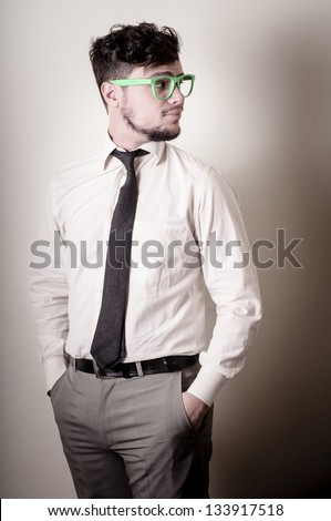 Sexy stylish businessman adjusting tie on gray background - stock photo