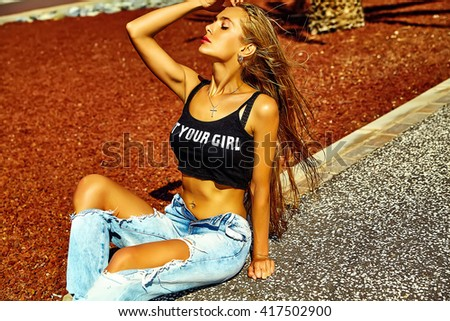 Sexy stylish hot beautiful young blond fashion woman model in summer  hipster clothes ripped jeans sitting in the street touching her flying hair - stock photo