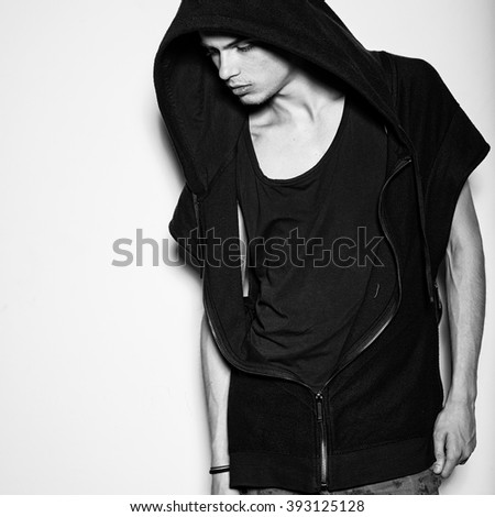 Sexy stylish man in the hood in the studio black and white portrait - stock photo