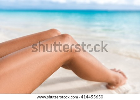 Sexy suntan bikini woman legs relaxing lying down on white sand beach summer vacation. Beauty skincare sun aging protection body care of tanned skin. Epilation laser or shaving concept. - stock photo