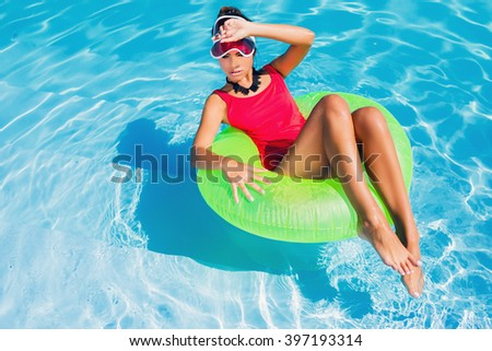 Sexy tamed woman in red swimsuit having fun and enjoying   summer in amazing big swimming pool. Young pretty girl  swimming on inflatable ring.  Stylish transparent cap.Beach party.  - stock photo