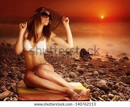 Sexy tanned model posing on the beach on red dramatic sunset background, stony coastline, fog over sea, seduction and beauty concept, summer vacation