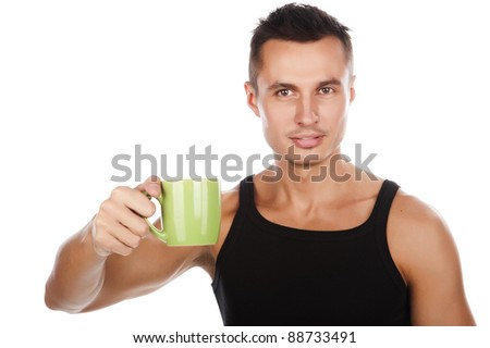 sexy tanned young guy in a black T-shirt with a mug in hand, drinking a hot beverage, isolated over white - stock photo