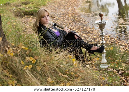 sexy thick of young blonde smokes a hookah in nature