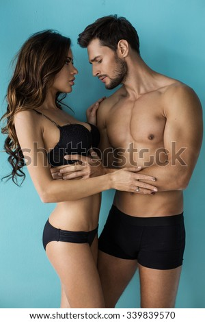 Sexy undress couple touching each other. Handsome man looking at the breast - stock photo
