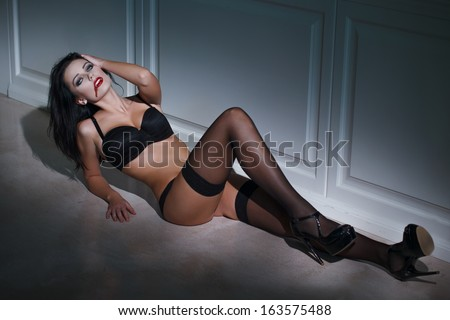 Sexy vampire woman laying on the floor  - stock photo
