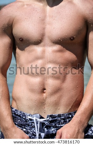 Sexy wet muscular torso of a young guy in the ocean in a swimming trunks