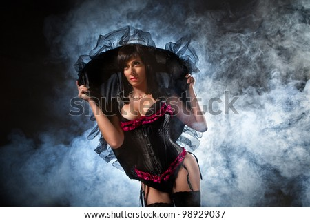 Sexy witch dressed up in black corset covered in smoke