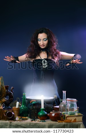 Sexy witch on a dark background making potion on wizard kitchen