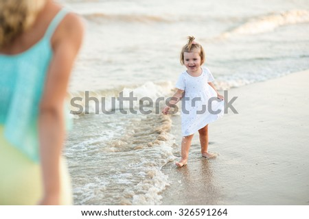 Sexy woman and little girl in a dress playing on the beach together.