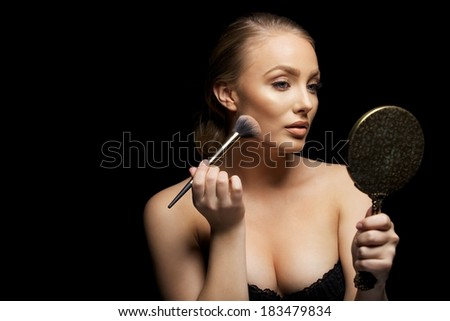Sexy woman applying foundation on her face with a make up brush. Caucasian female fashion model holding mirror applying make up against black background. - stock photo