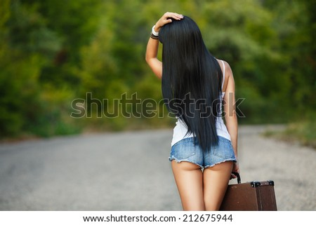 Sexy woman body in jean shorts. The model is back.Lonely girl with suitcase at country road.. - stock photo