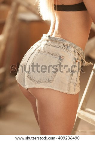 Sexy woman body in jeans short. Great ass. Fit  buttocks. Sunny color. - stock photo