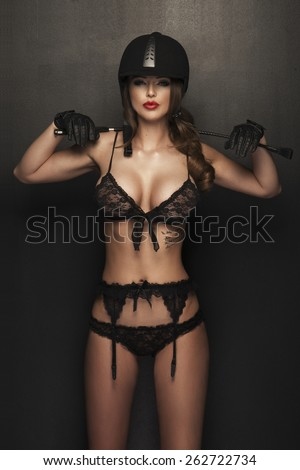 Sexy woman body with whip and helmet like jockey  - stock photo