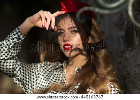 Sexy woman brunette long hair poses in red garrison cap with black veil on sunny day on dark background